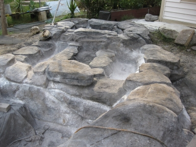 Unfortunately I only have a few pictures of this process - none of them do it any justice.  This is the most tedious part of building a rock pool.  Step 1 - spread thick layer of high durability latex over available, real rocks with good texture - a few coats Step 2 - Mix concrete in mixer, use browns, yellows, gray's and black concrete stain powder to get desired color - pay attention to your recipe, so it doesn't vary day to day Step 3- each load of (3 shovels of portland and 10 of sand - if i rememeber) concrete makes 1-2 rocks depending on size.  Step 4 - shape the rock with trowel and lightly dust with additional concrete stain - exress your rock-self here, do a Google search for rocks and copy - for me it was difficult to be random - let dry for 30 min (if hot outside, keep moist with light water spray) Step 5 - Coat rock with 1 part zinc stearate, 1 part potassium powder - releasing agent Step 6 - While still maleable, take latex form and pat texture into outside of rock.  The releasing agent allows you to remove latex forms without pulling concrete off.  Wash, rinse, repeat about 1---200 times. .